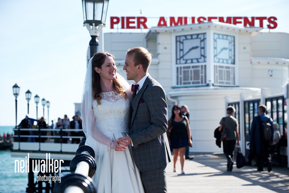 the bride and groom lean against a railing together with Pier Amusements sign in the background