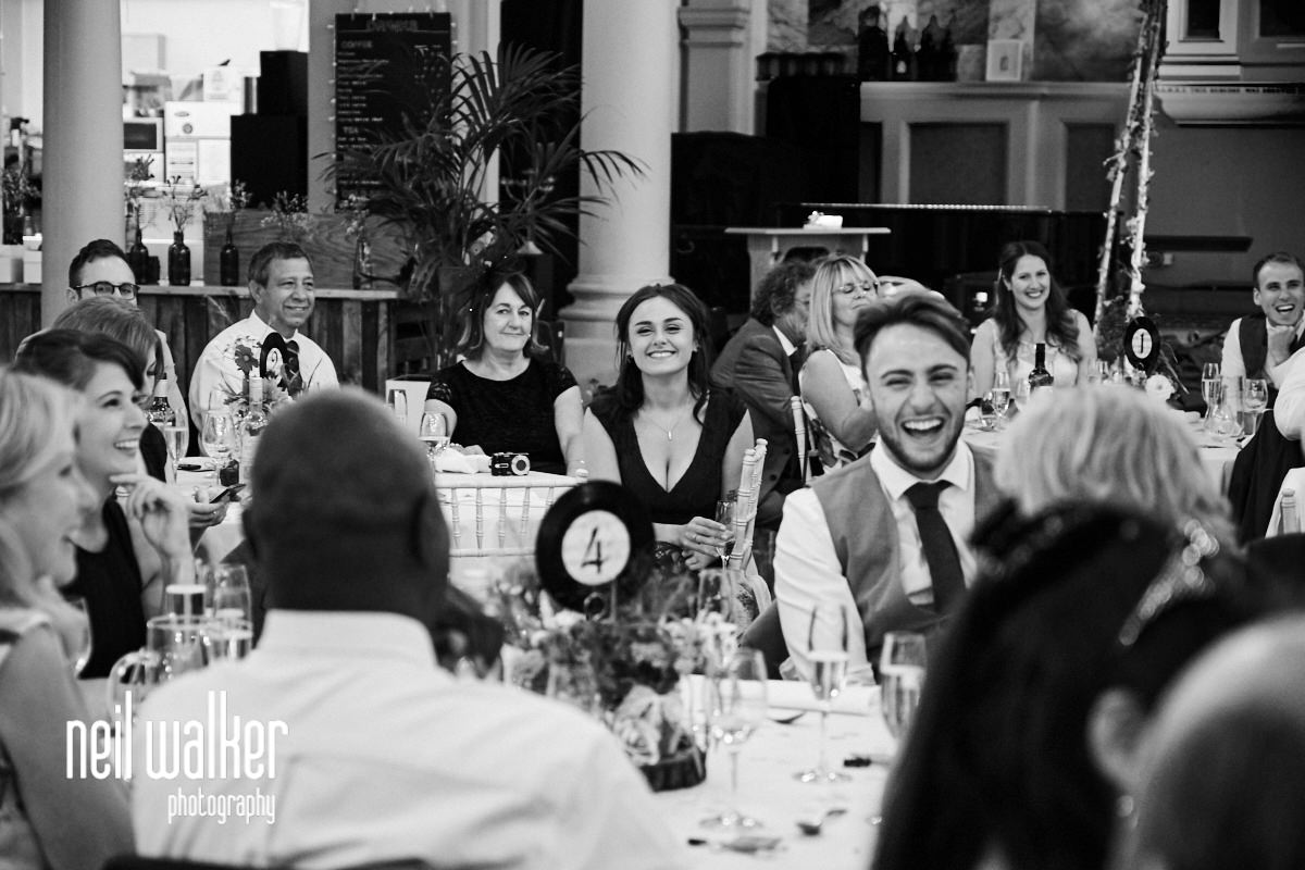 a bridesmaid laughing at the best man's speech