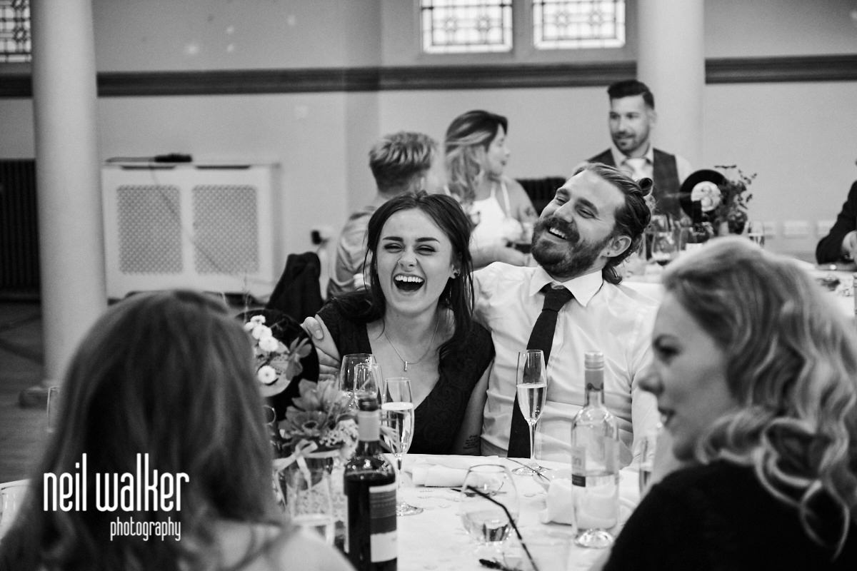 a bridesmaid and an usher laughing