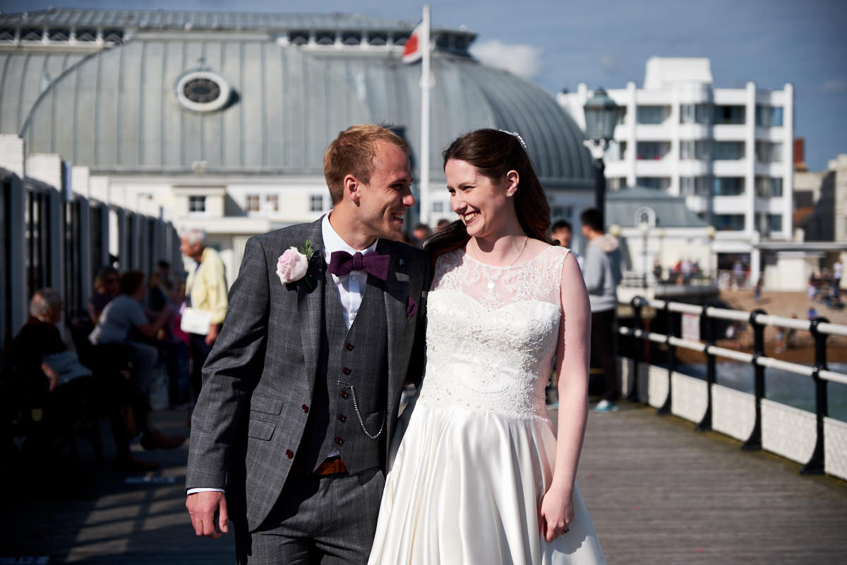 a bride and groom from a St Paul's Worthing wedding, walking along Worthing Pier
