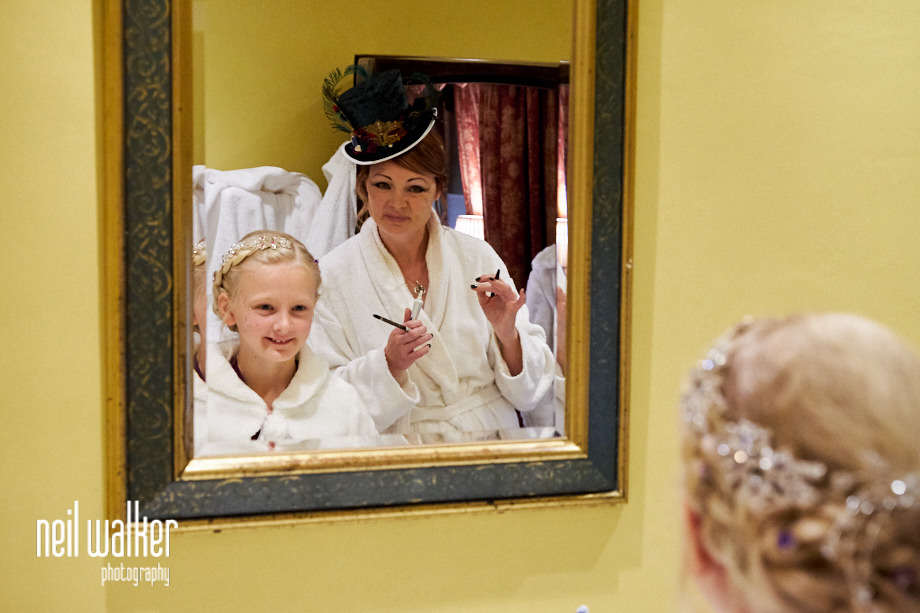 the bride and a bridesmaid looking in the mirror