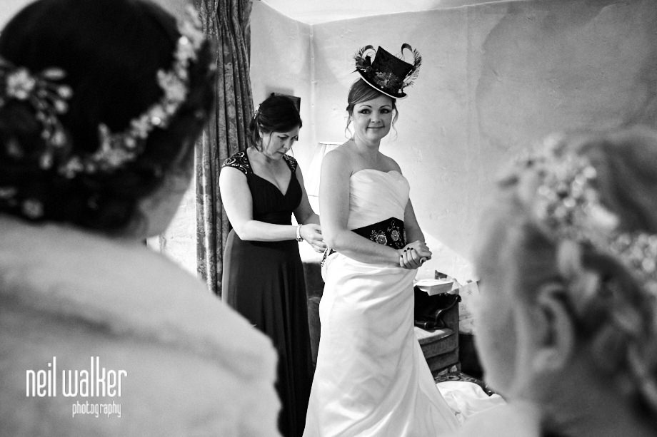 the bride having her dress done up