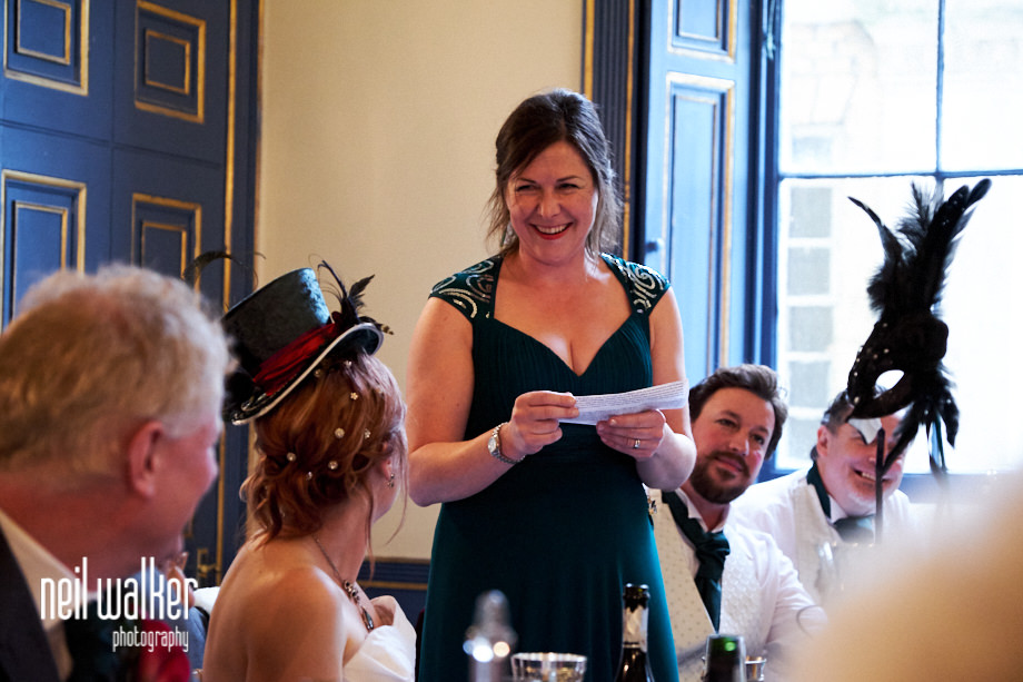 the chief bridesmaid smiles at the bride during her speech
