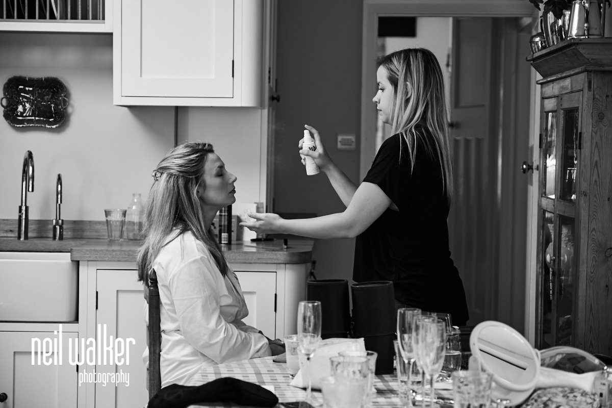 the bride having hair spray applied