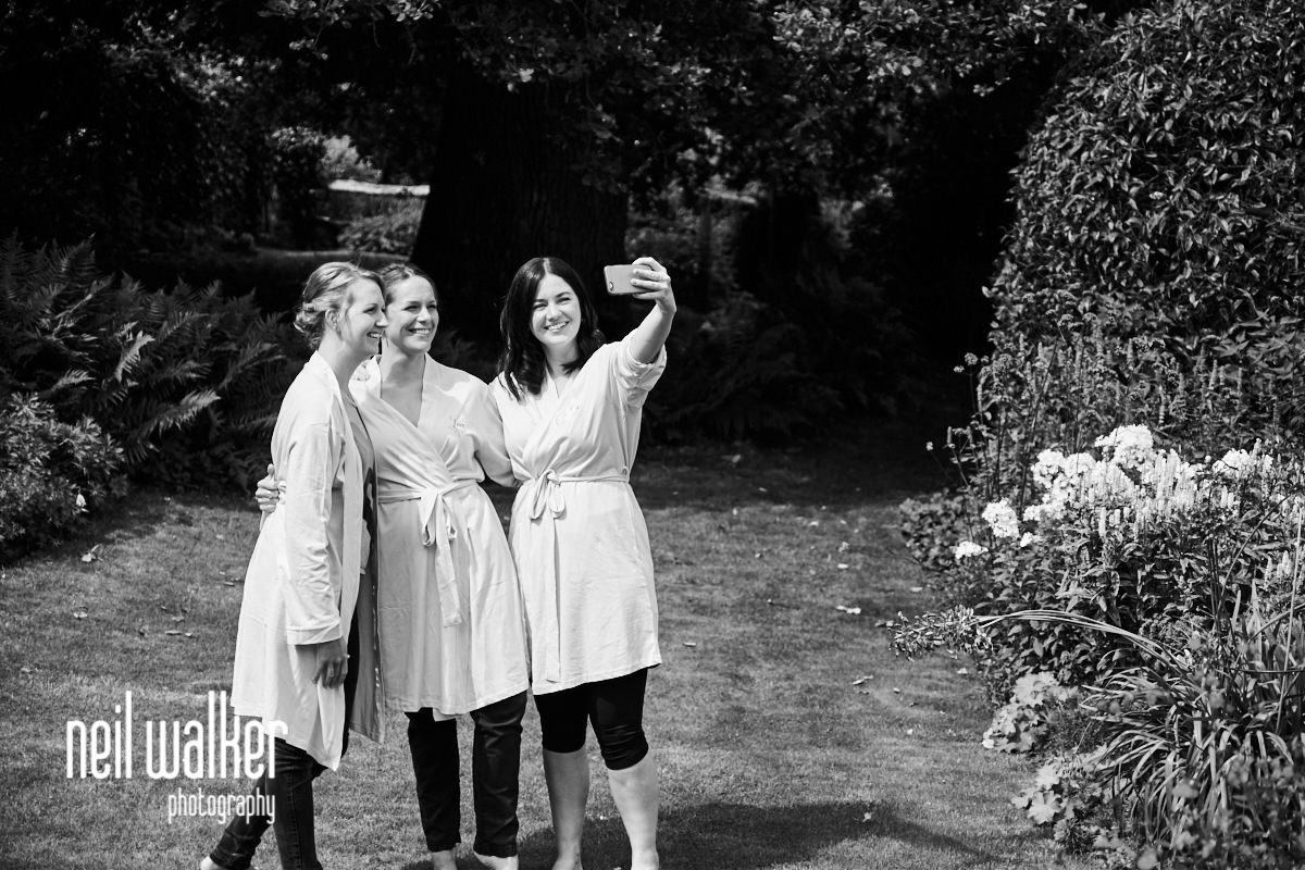 the bridesmaids taking photographs of themselves in the garden