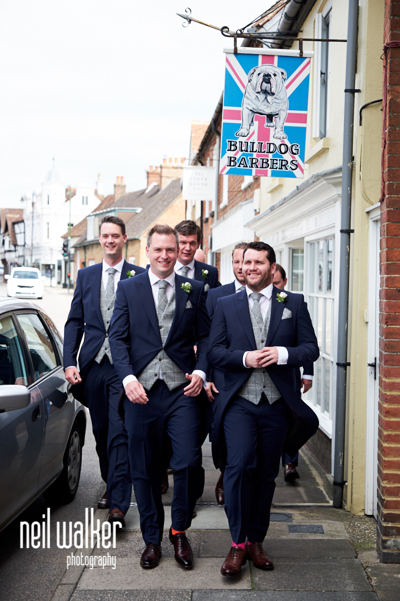 the groom and ushers walking under a sign for a shop