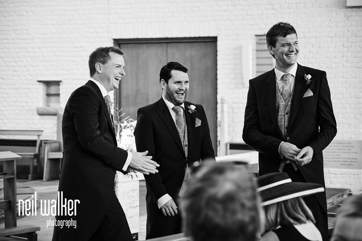the groom laughing with his best man and an usher