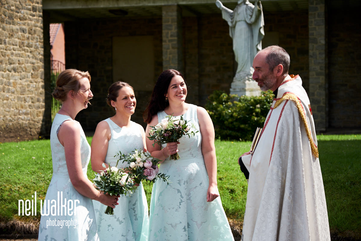 the bridesmaids talking with the priest