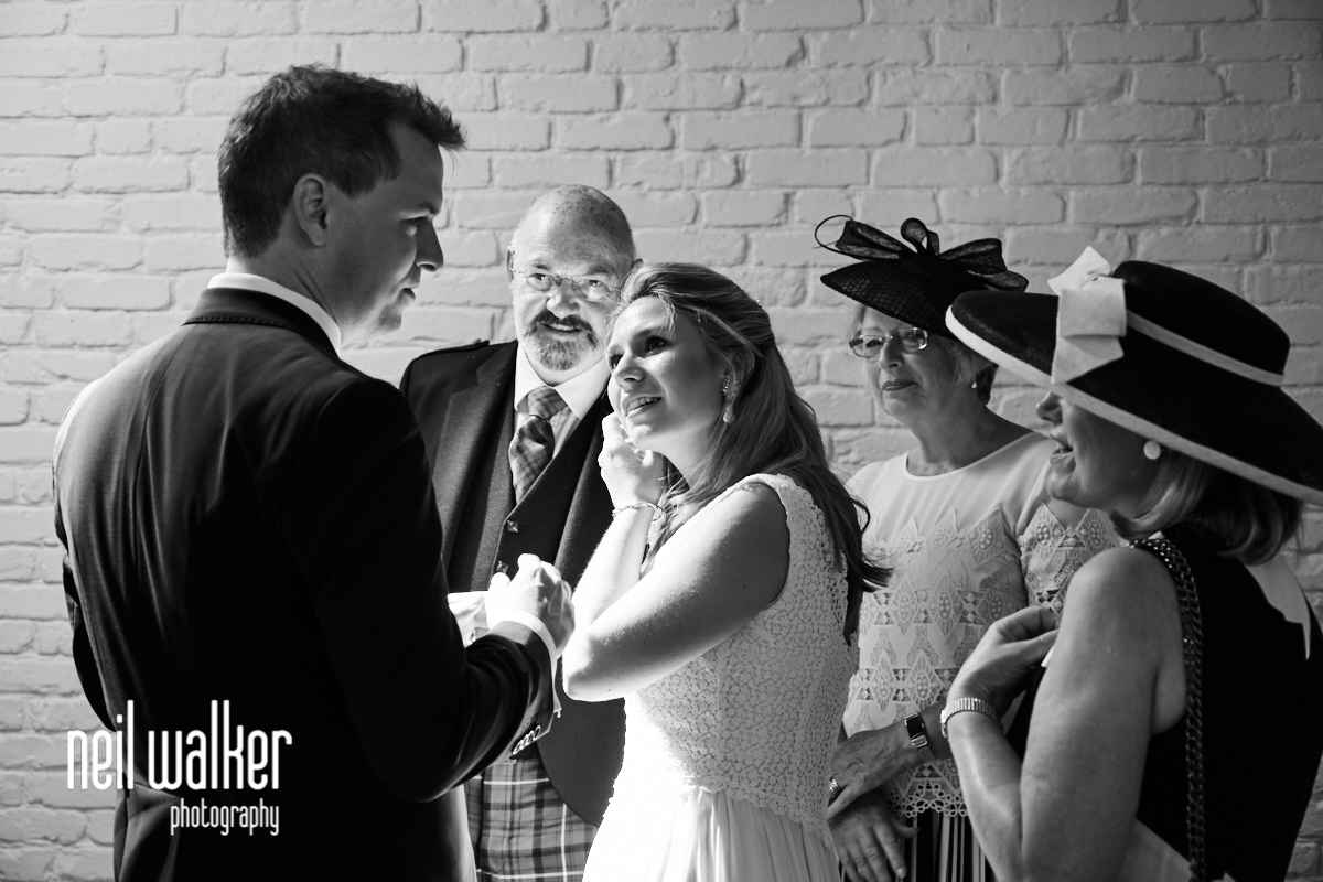 the bride and groom talking during the signing of the register
