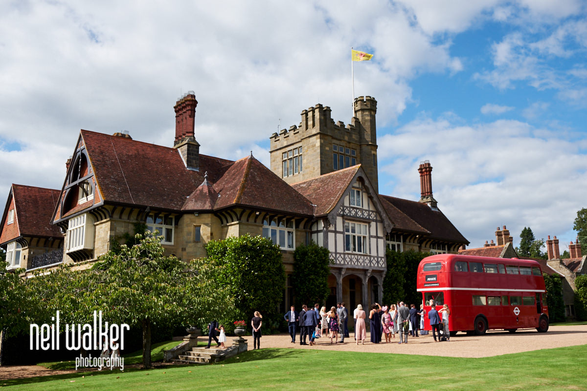 exterior of Cowdray House with guests and a red bus
