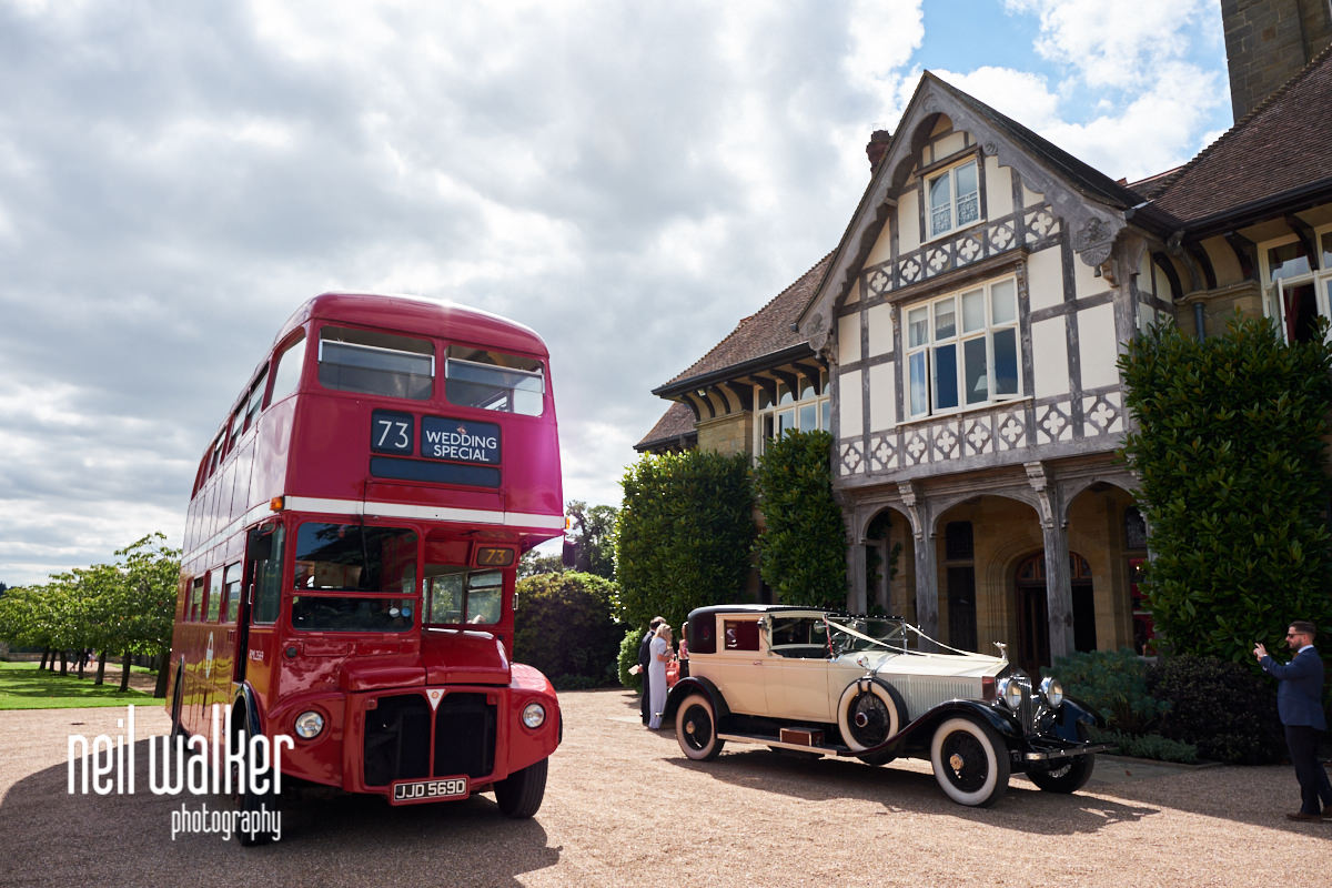 exterior of Cowdray House with a red bus and the wedding car