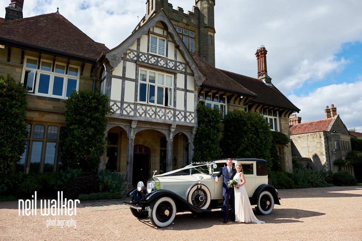 exterior of Cowdray House with the bride and groom by the wedding car