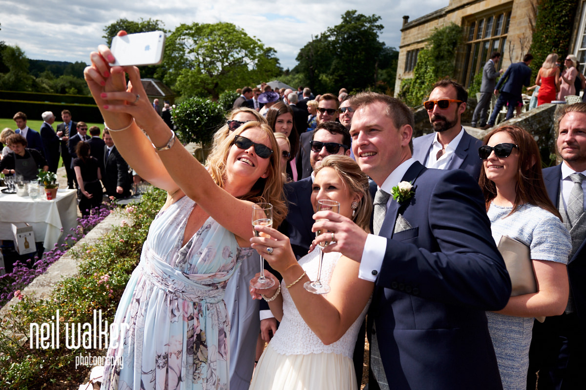 guests taking a photograph with the bride and groom at Cowdray House in West Sussex