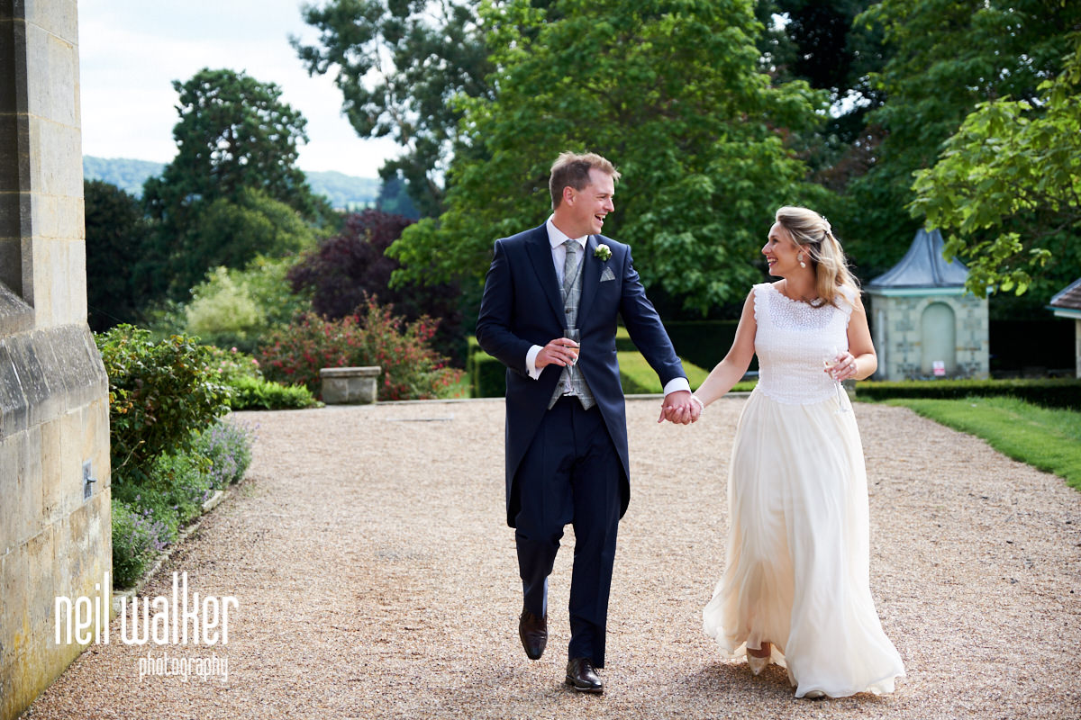 the bride and groom walking together int he grounds of Cowdray House in West Sussex