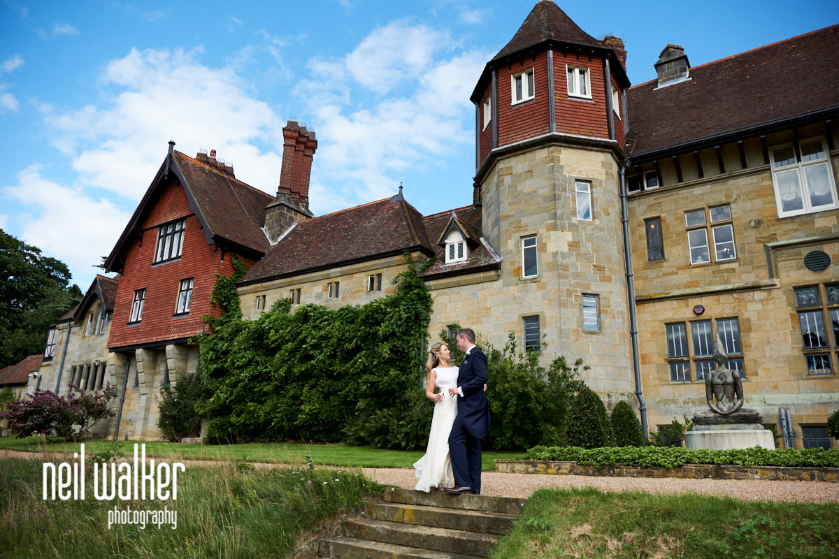 the bride and groom with Cowdray House in the background
