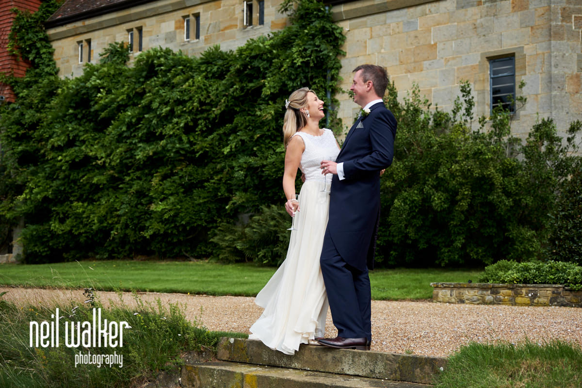 the bride and groom laughing as they stand in front of Cowdray House