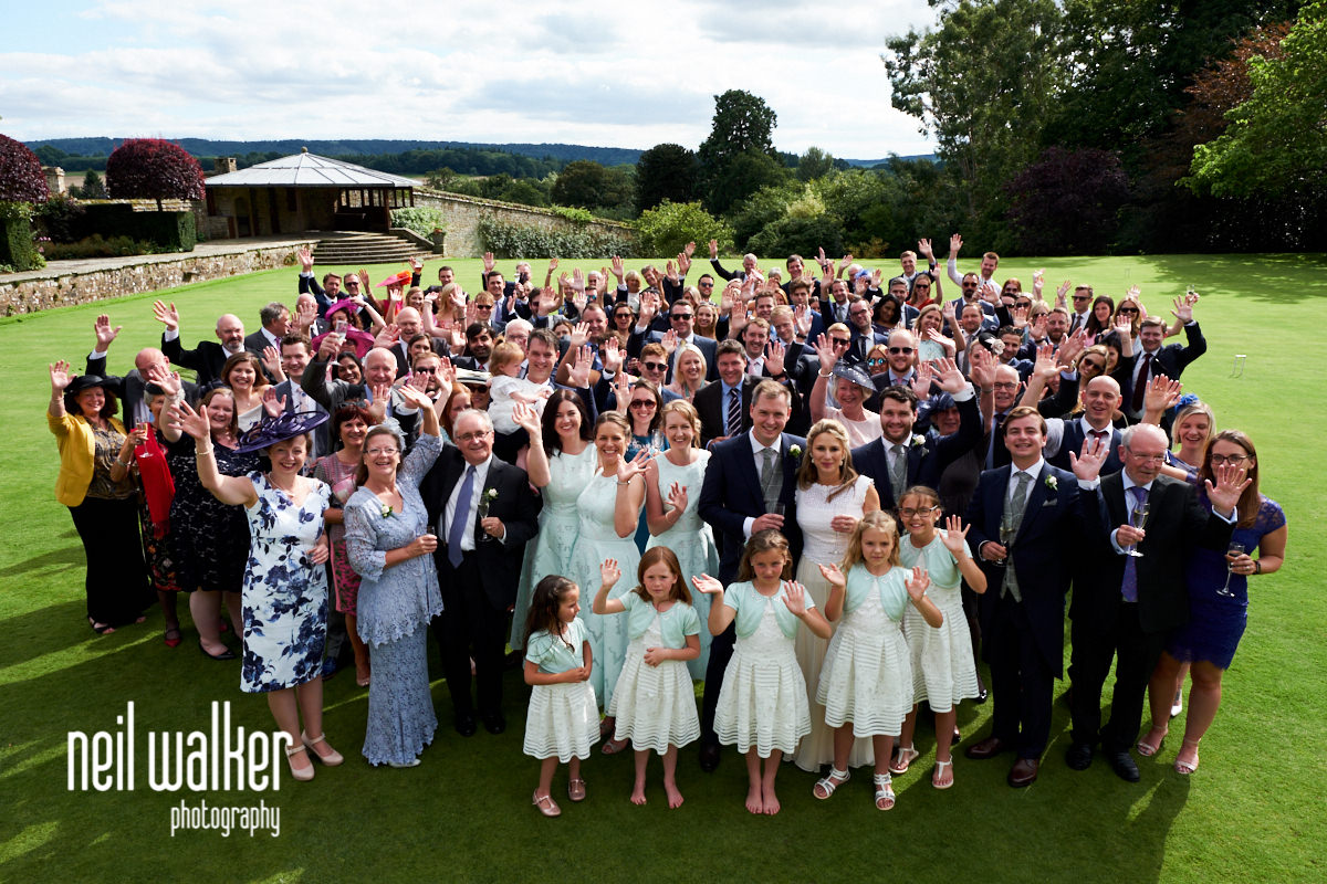 a big group shot of all the guests at a wedding at Cowdray House in West Sussex