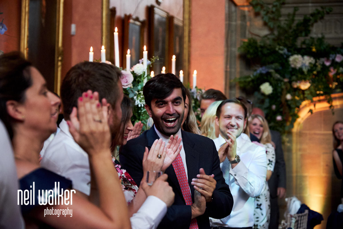guests cheering as the bride and groom are announced into the wedding breakfast at a summer wedding at Cowdray House in West Sussex