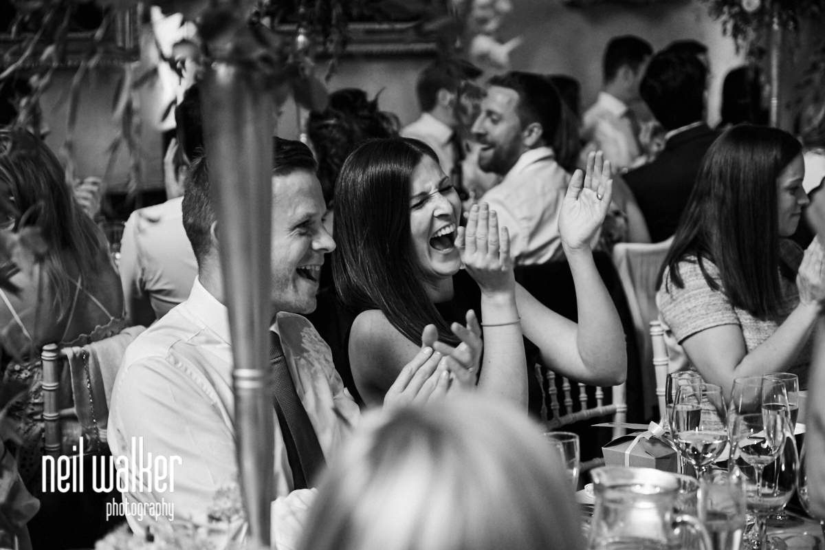 a guest laughing as she cheers the bride and groom