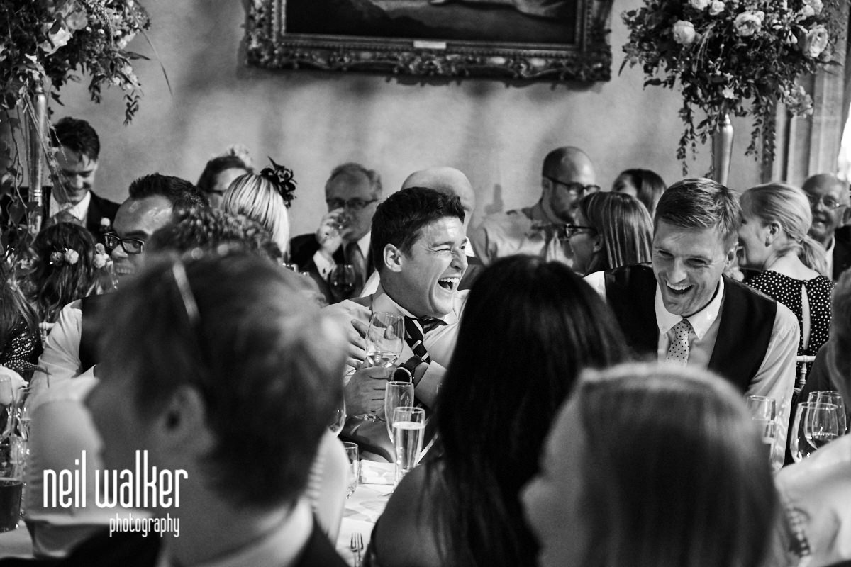 a guest laughing at the speeches at a Cowdray House wedding