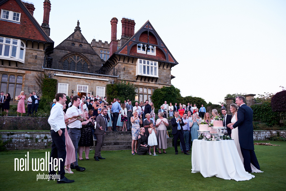 the bride and groom cutting their wedding cake at a Cowdray House wedding