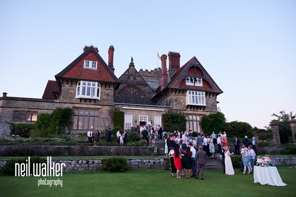 guests at a wedding with Cowdray House in the background