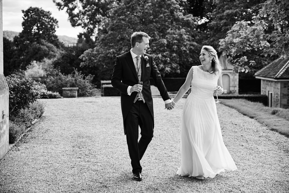 a bride and groom walk and laugh together during their wedding at Cowdray House in West Sussex