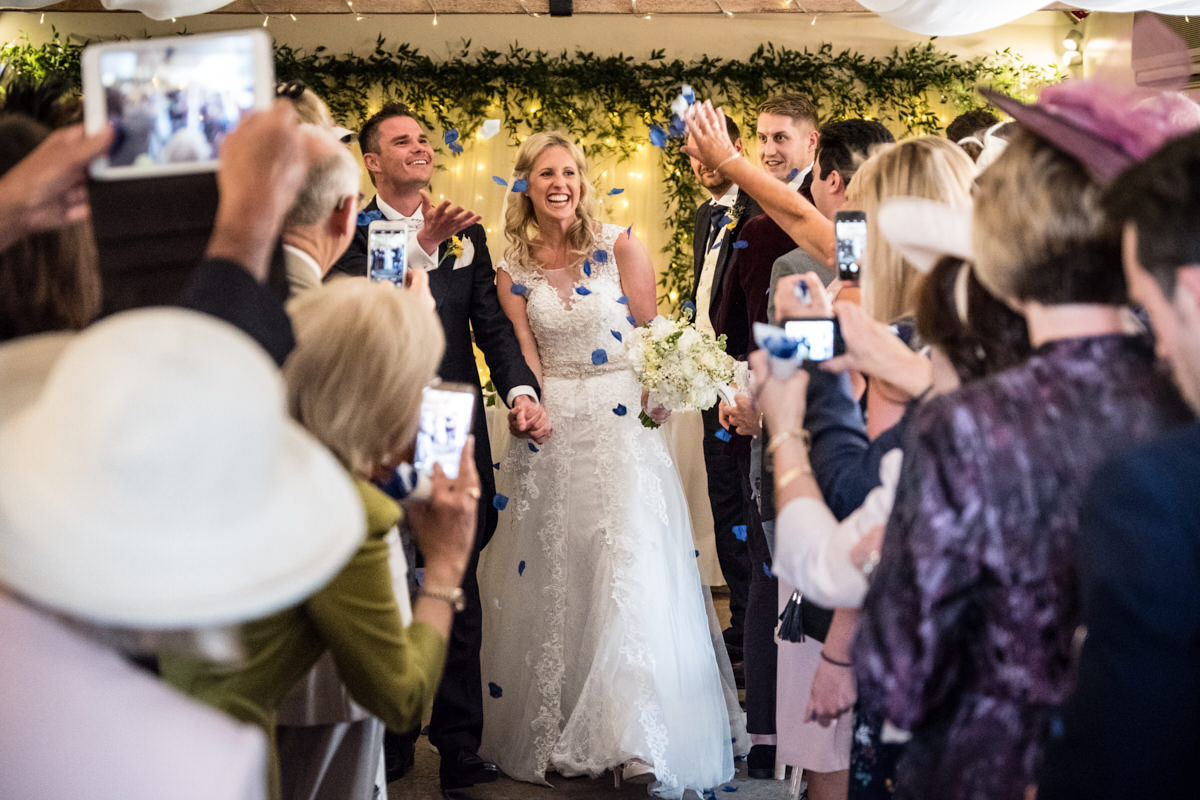 a bride and groom having confetti thrown at them during their recessional at Farbridge
