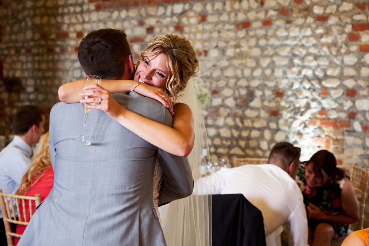 a bride hugging her brother during her wedding reception