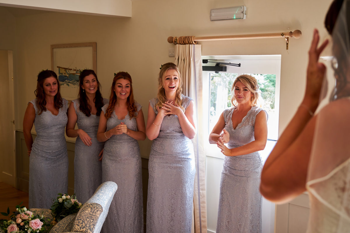 bridesmaids laughing and crying seeing the bride in her dress for the first time