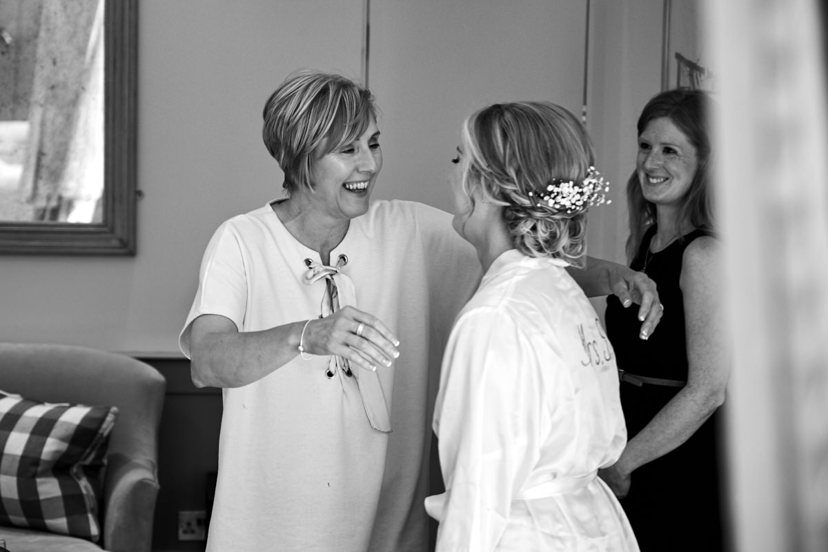 the mother of the bride throwing her arms around her daughter while they get ready for her wedding