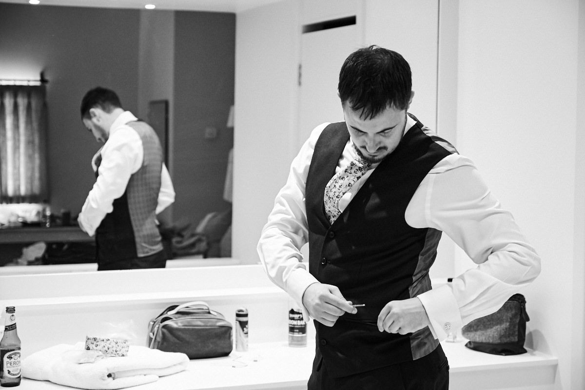 the groom doing up his waistcoat