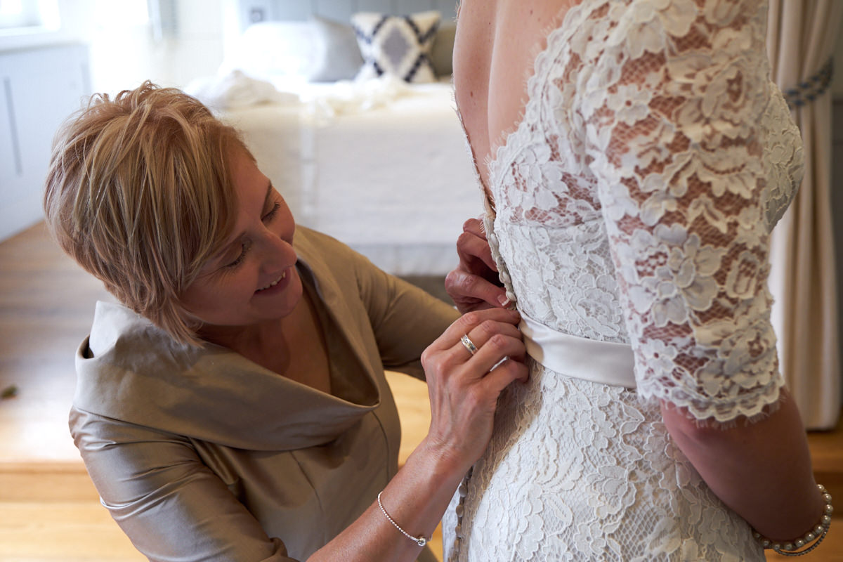 the bride's mother doing up the buttons on the bride's dress