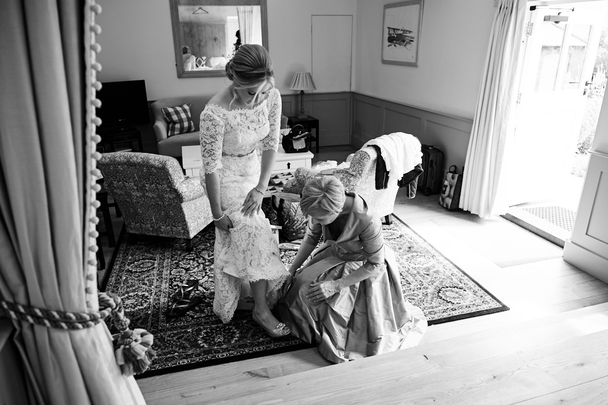 the bride's mother putting on her wedding shoes