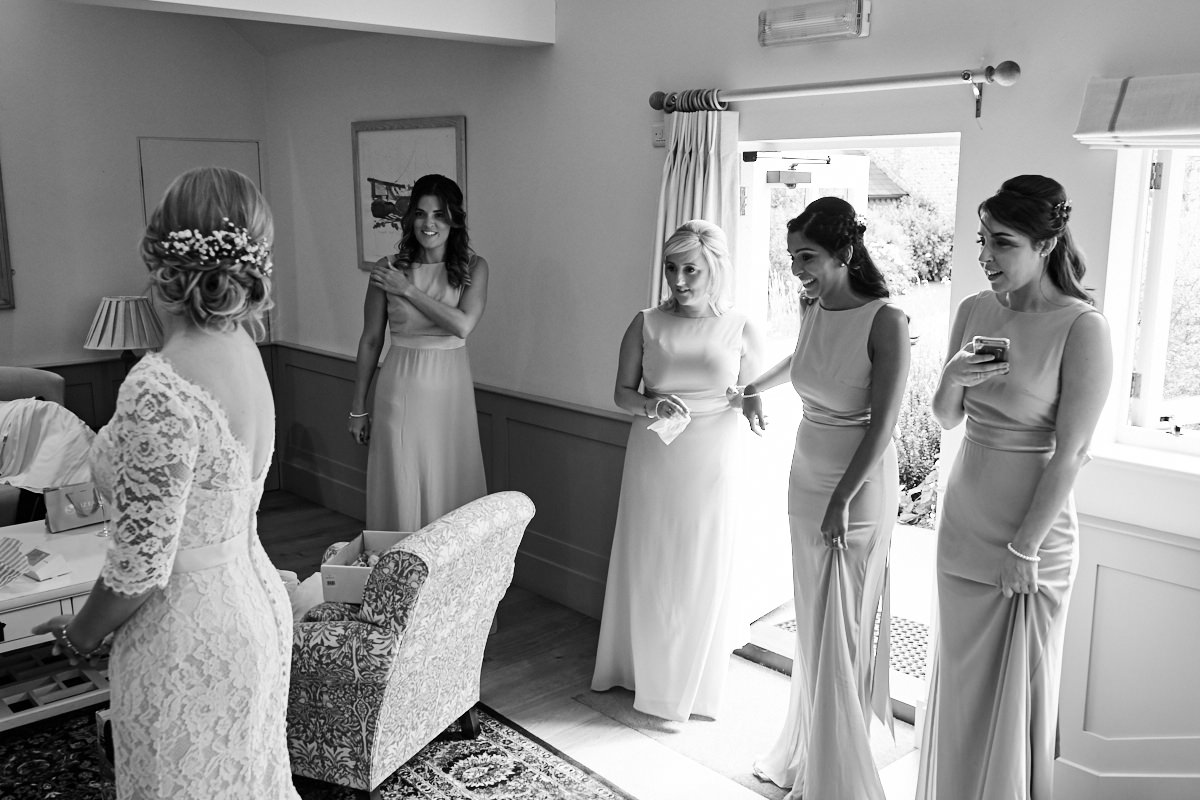 the bridesmaids looking at the bride's wedding dress