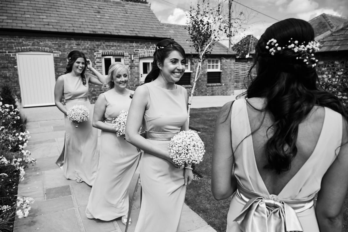 the bridesmaids walking to the ceremony barn for the bride's wedding ceremony