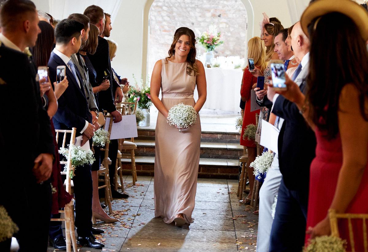 a bridesmaid walking down the aisle