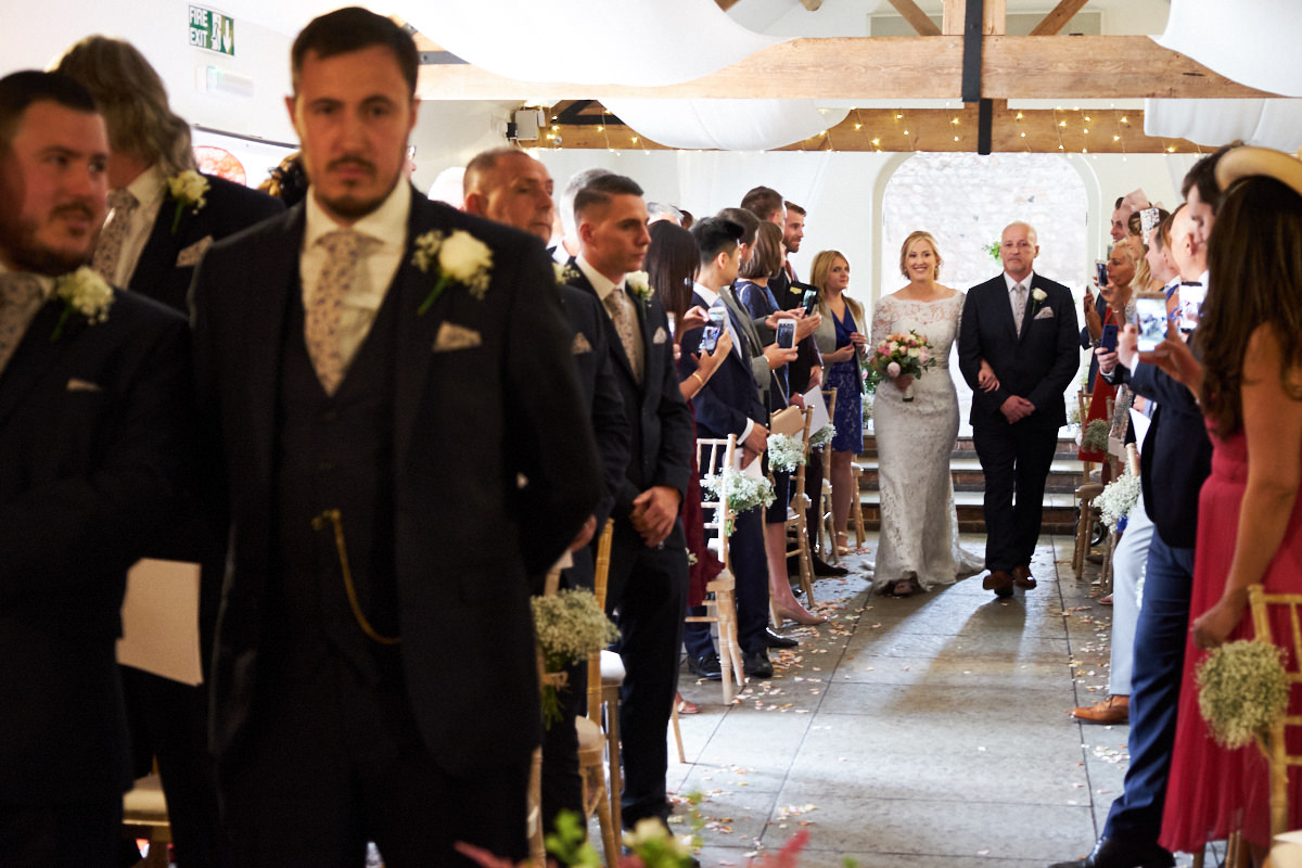 the bride walking down the aisle to her groom at a barn wedding