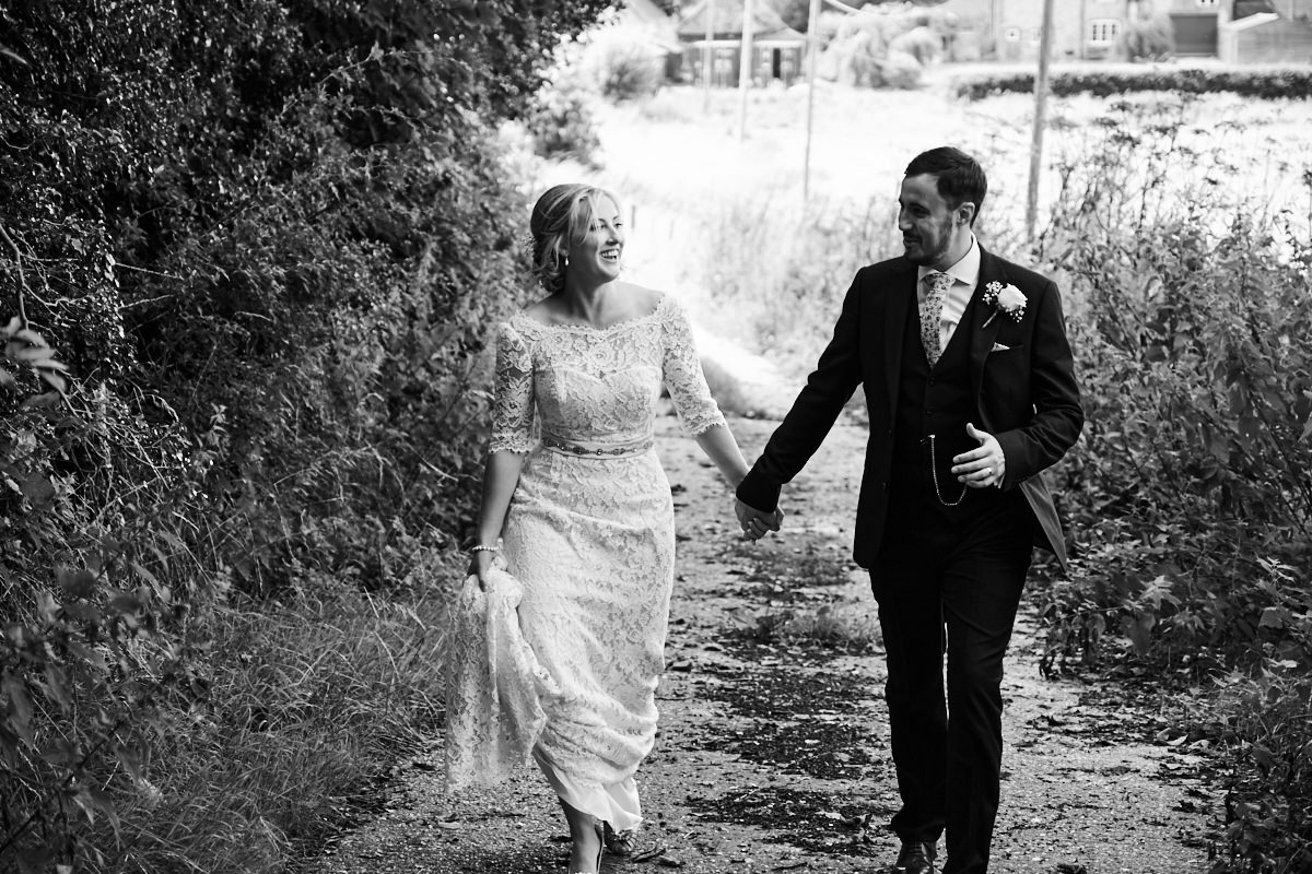 the bride and groom walking towards a farmyard