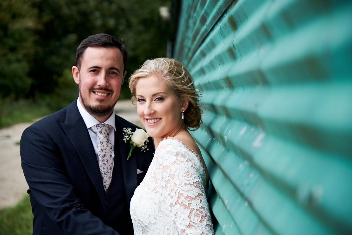 the bride and groom by a farm building made of green corrugated iron