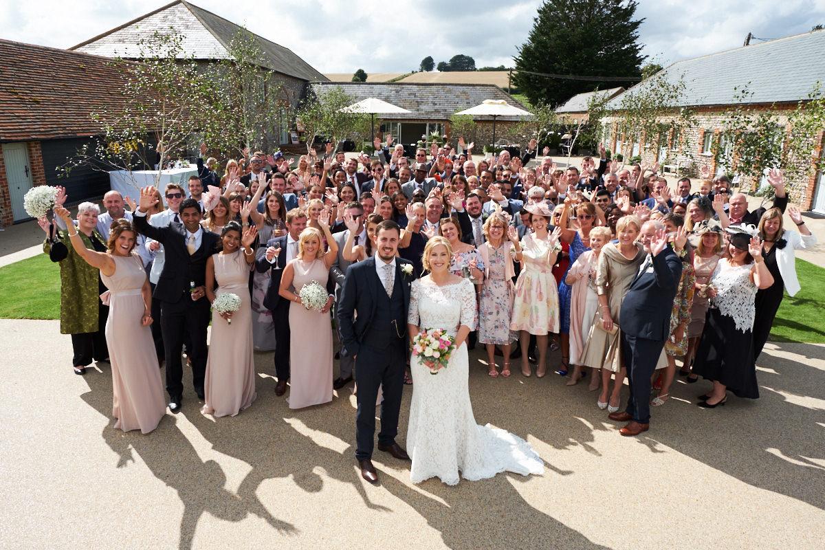 a big group shot at a barn wedding