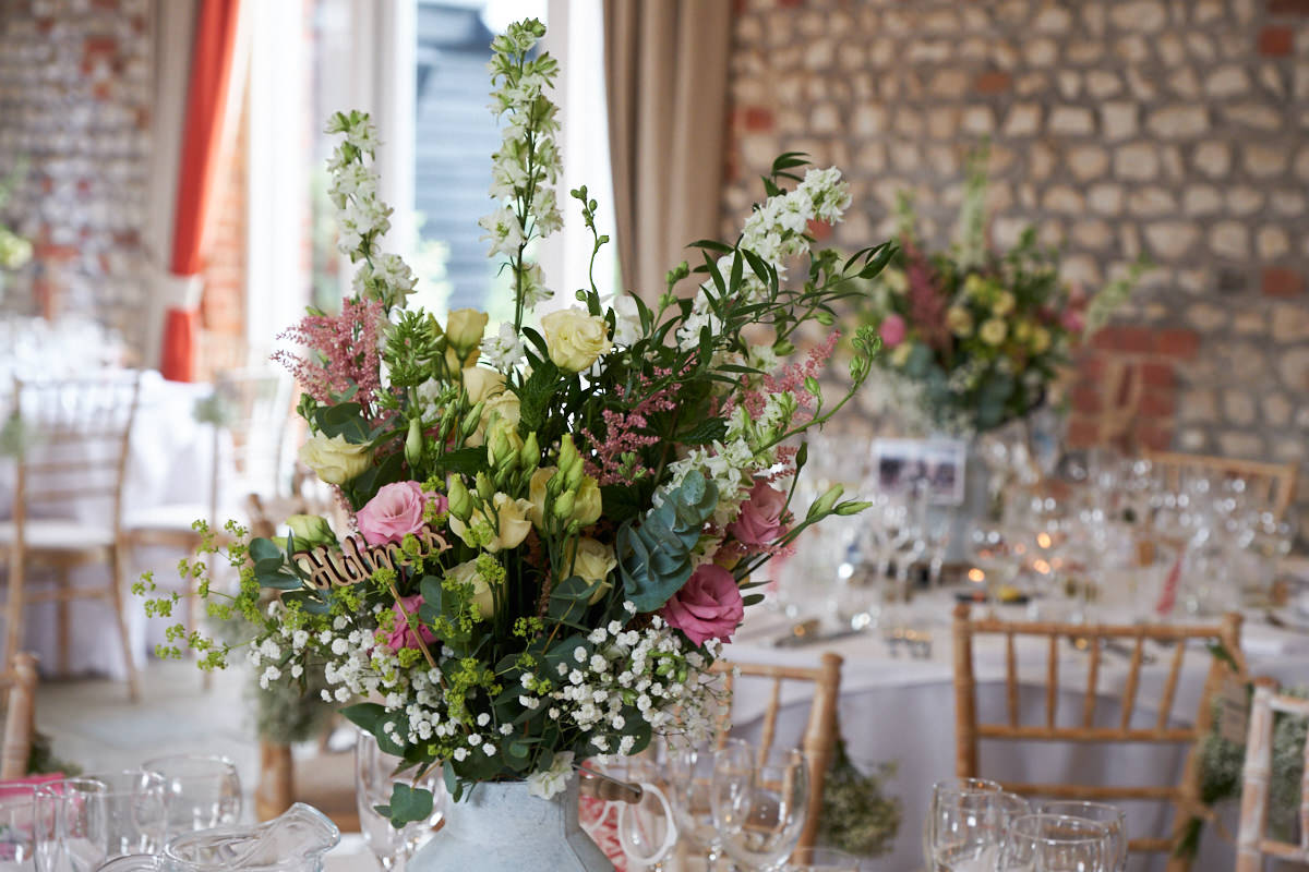wedding flowers as centre pieces on the tables at a barn wedding