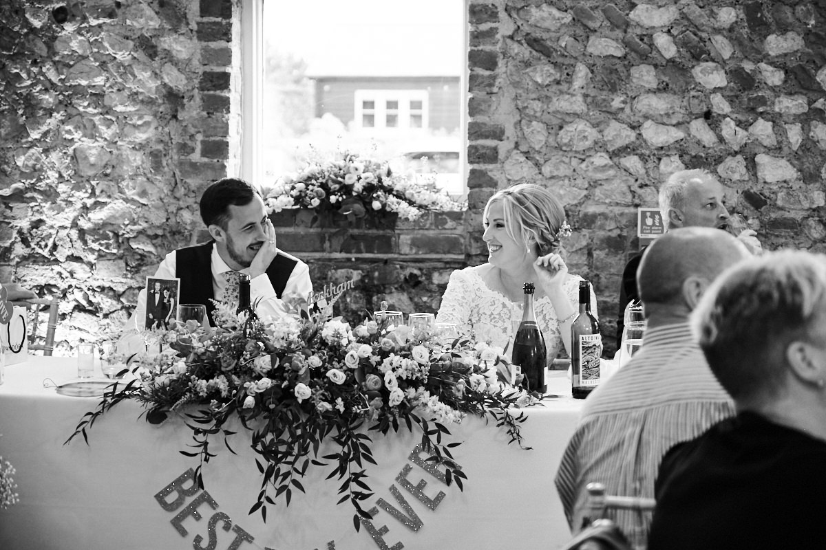 the bride and groom look at each other during the speeches at their barn wedding