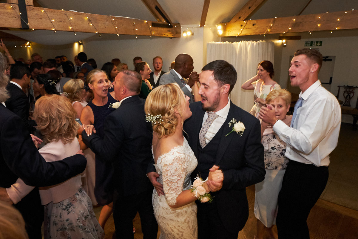 the bride and groom dancing with guests at their Sussex barn wedding