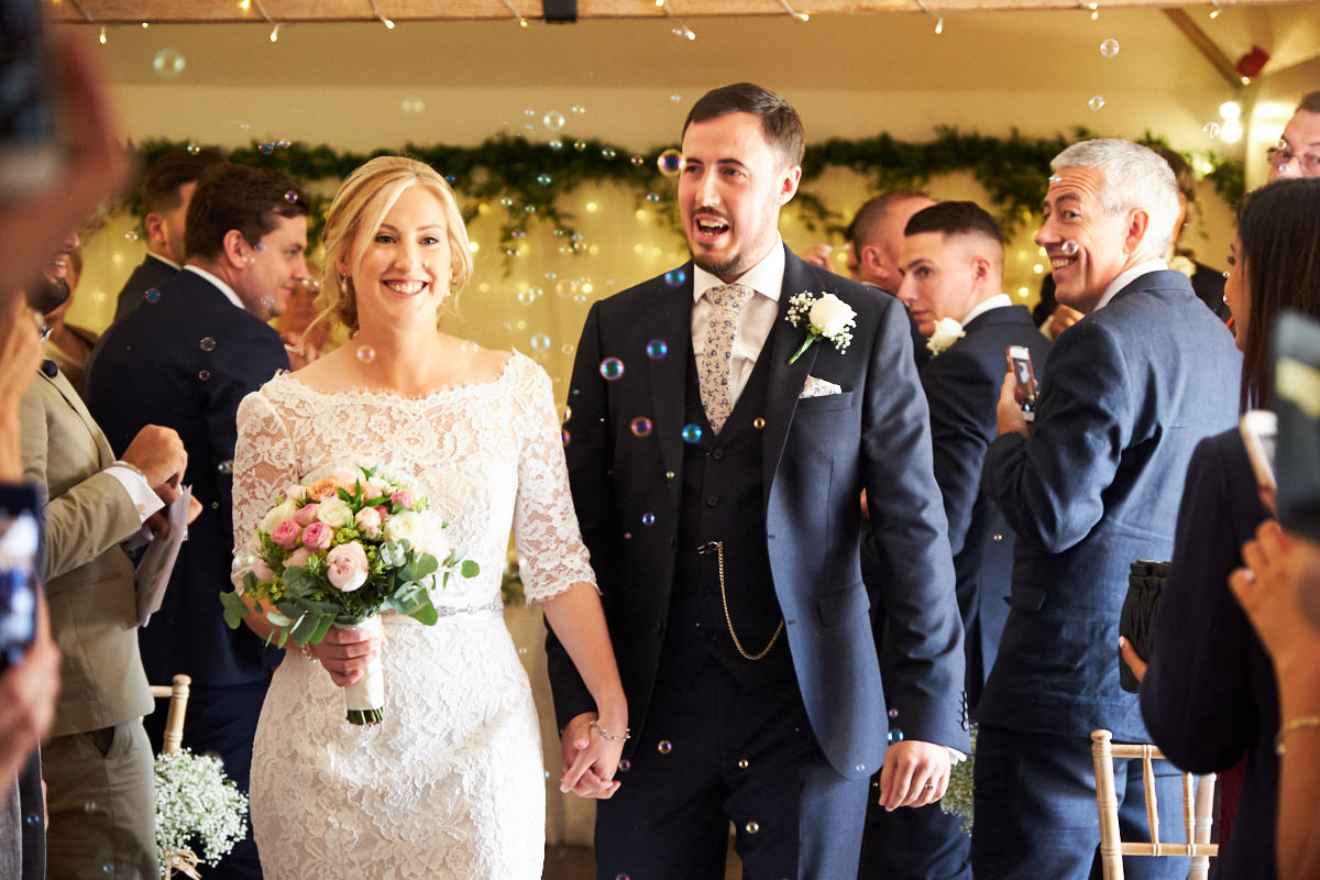 a bride and groom at their barn wedding in West Sussex walking down the aisle together