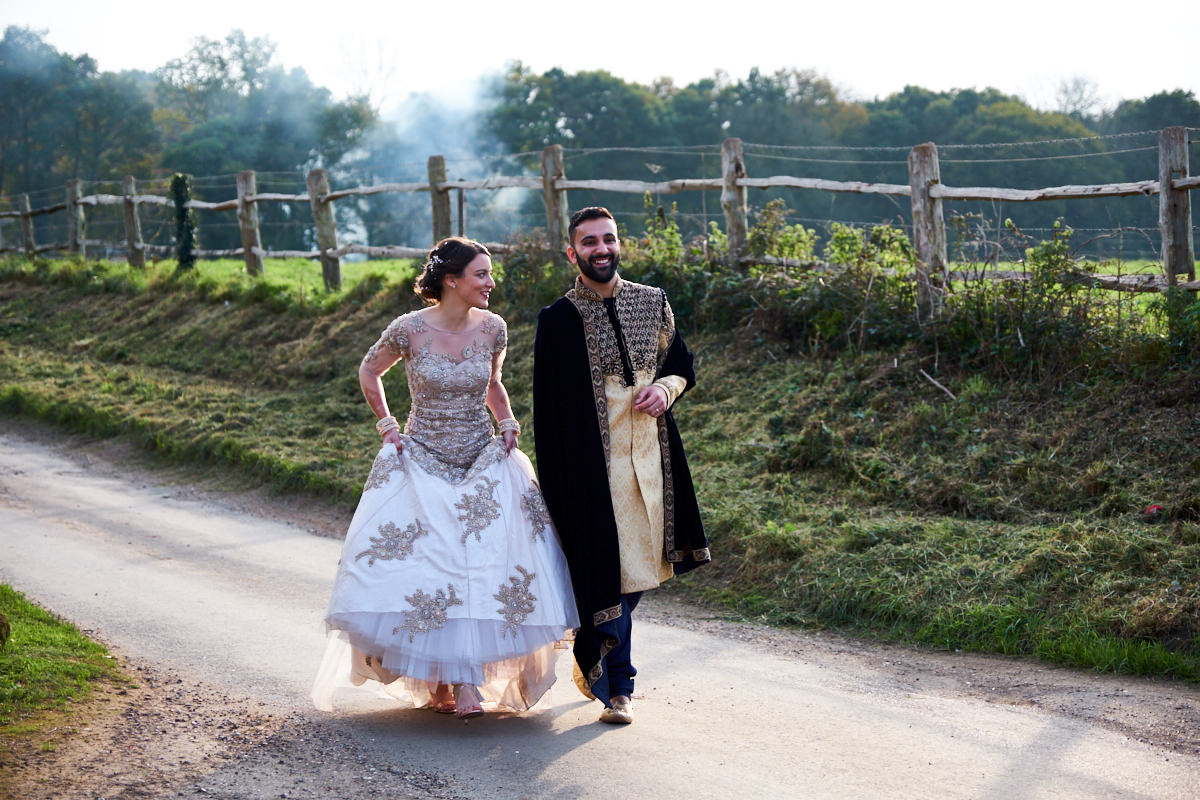 a bride and groom laugh as they stroll down a country lane during their Sussex wedding