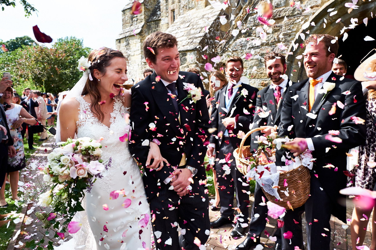 a bride and groom walking while their guests throw confetti