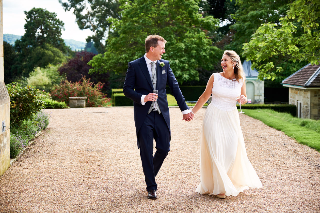 a bride and groom walking and laughing together on their wedding day