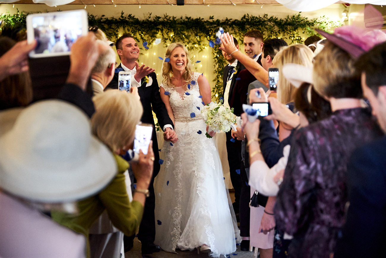 guests throw confetti while the bride and groom walk down the aisle after their wedding ceremony