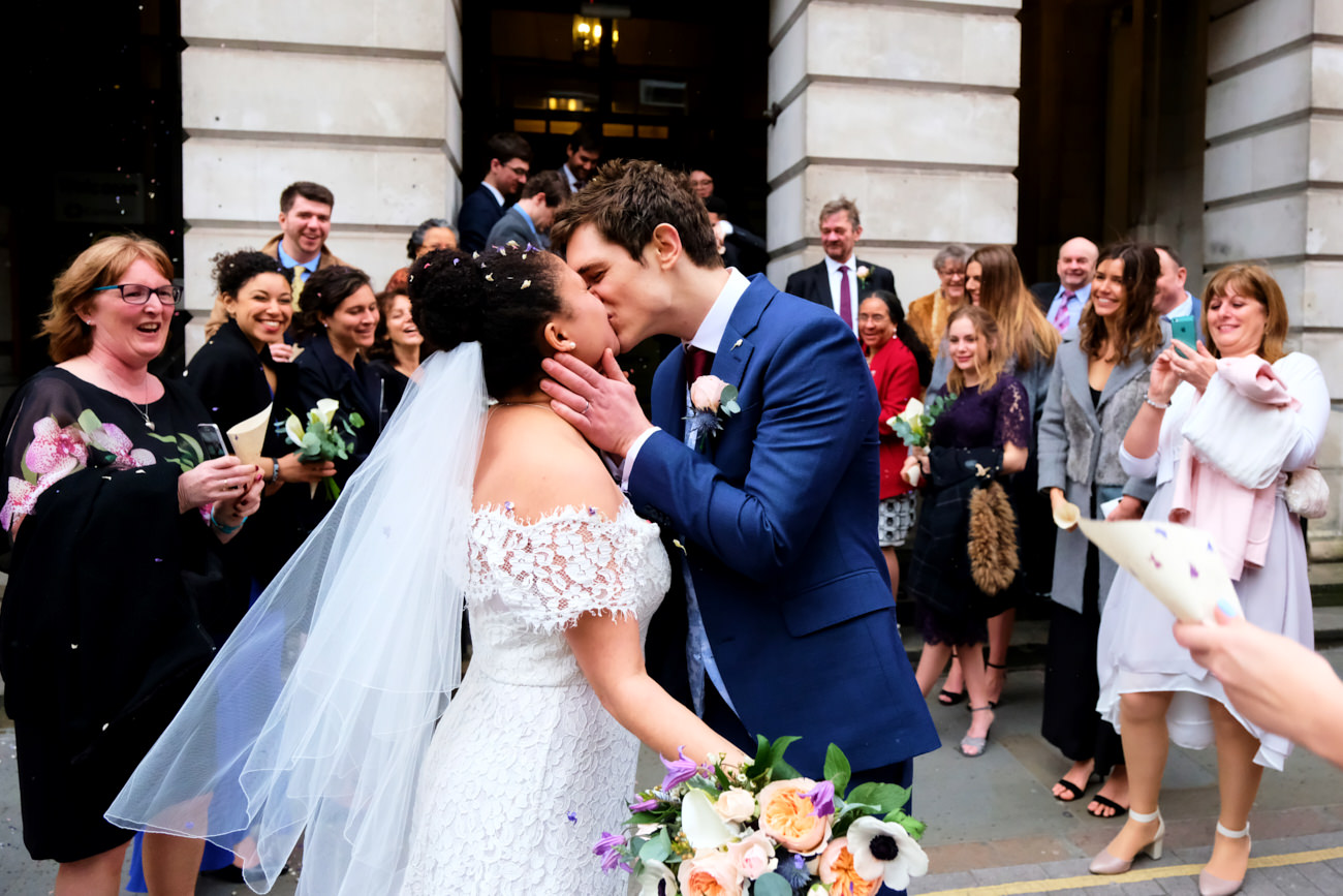 The bride and groom share a kiss while guests laugh and cheer them